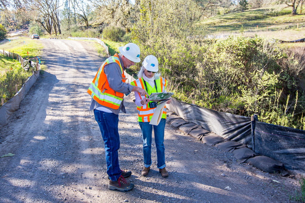 Description of . Private road to local ranches that is now in the footprint of the bypass. This is a one of the many creek crossings. CalTrans worker discusses map with The Willits News Publisher Debbie Clark. Photo by Steve Eberhard.