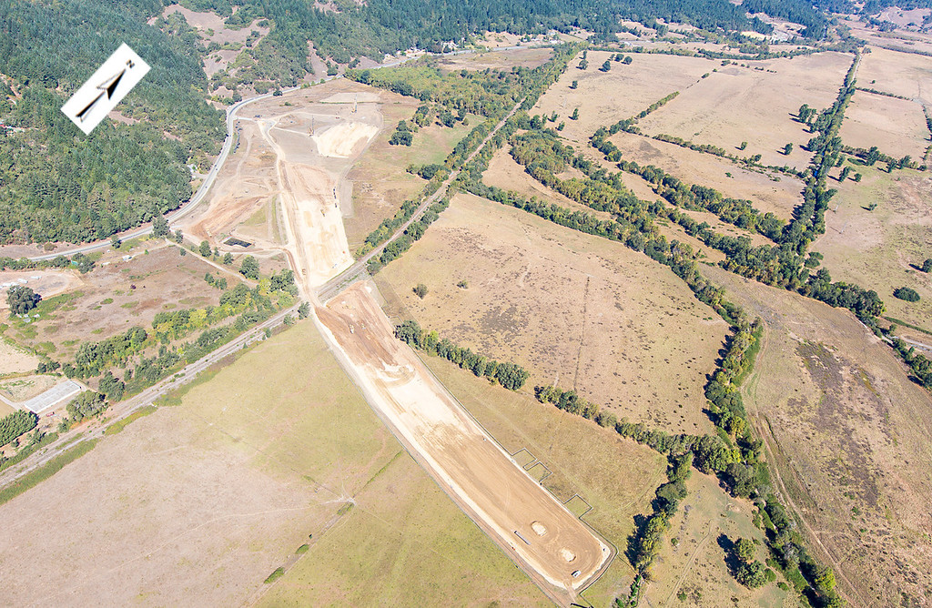 Description of . A photo showing the path of the bypass route from the northern interchange southeast to the start of the viaduct. Willits bypass construction overflight Sept. 5; Pilot Mike Smith; photographer Steve Eberhard/TWN