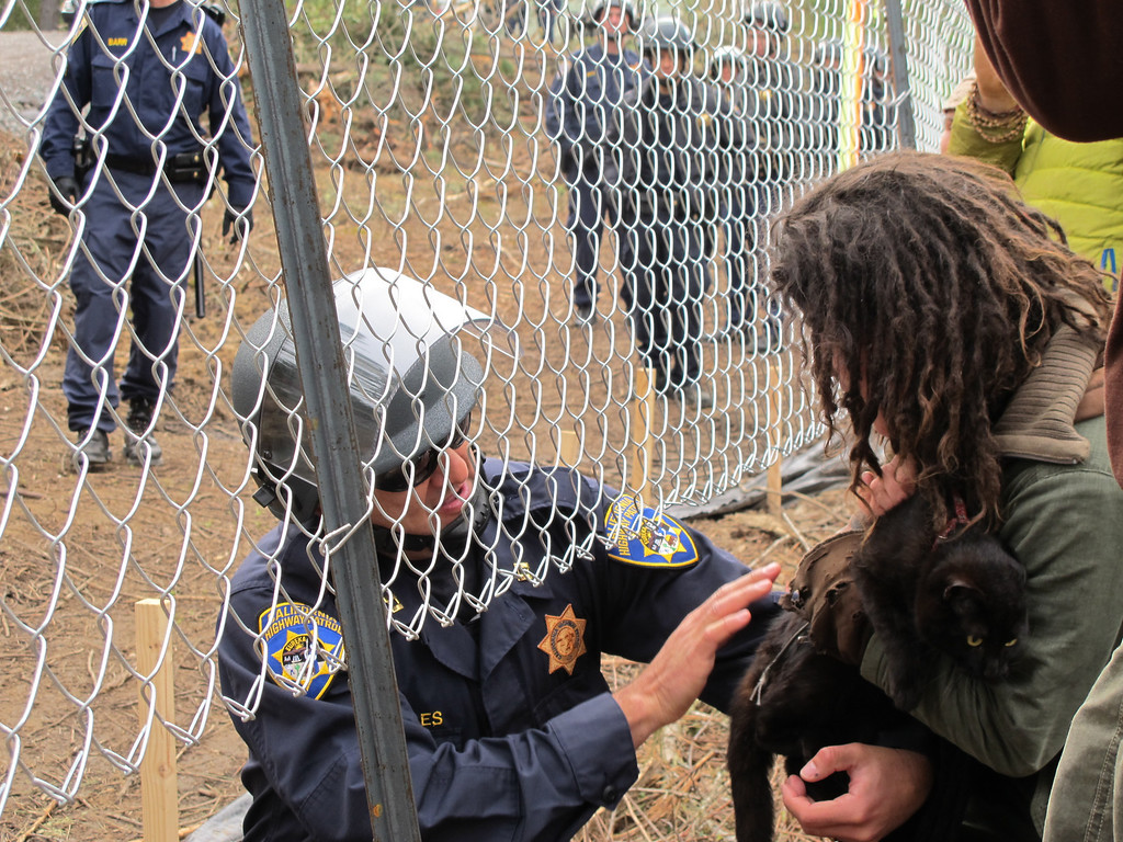 Description of . The officer gently hands off the rescued kitty to Tara. By The Willits News Publisher Debbie Clark