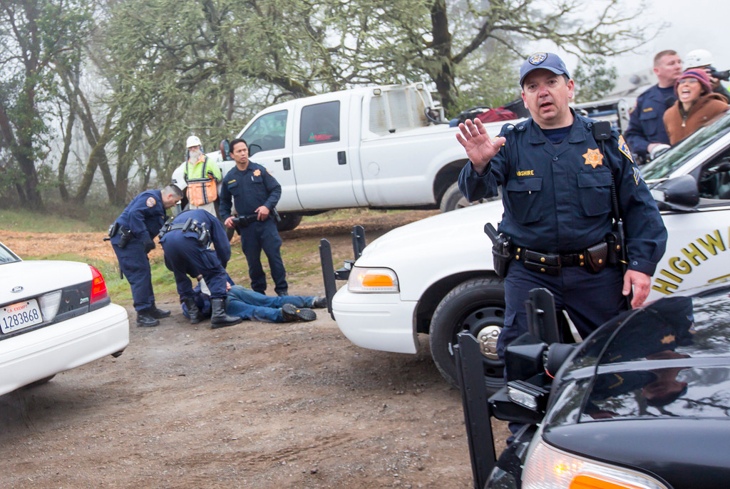 Description of . The Willits News photographer Steve Eberhard who was trying to photograph the treatment of Will Parrish, was told to return to the other side of the highway or he would also be arrested. Photo by Steve Eberhard