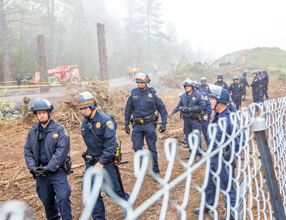 Description of . Large contingent of California Highway Patrol officers guarding the fence line near the location of the second and third tree sitters, Jean Daniel Weilbach and Martin Reign Katz. Photo by Steve Eberhard
