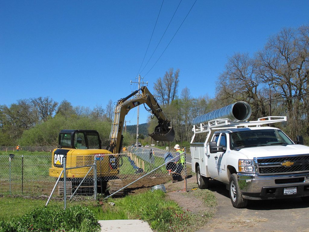 Description of . Workers installing a culvert and access to to the field on the south side of Hearst Willits Road.