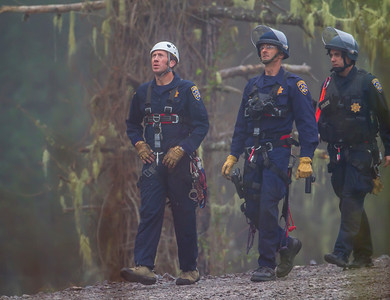"""CHP SWAT Unit approaches the man lift to remove Amanda """"Warbler"""" Senseman from her perch in a pine tree at the Willits Bypass construction site. Photo by Steve Eberhard"""