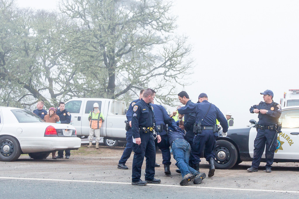 . Will Parrish being dragged to the side of the road to allow traffic to resume. (Sara Grusky has been zip tied and is awaiting placement in the patrol car. Photo by Steve Eberhard