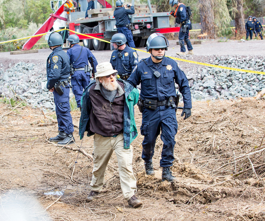 . One of the protesters being taken away by officers while the CHP operation against Katz and Weilbach is underway. He was the only person on the ground arrested at this location. Note the new road bed and muddy surroundings created since the first CHP operation on March 21. Photo by Steve Eberhard