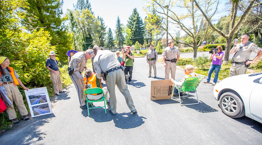 . CHP Officers arresting Priscilla Thimas, 76, of Ukiah. She told officers she was not going to move from in front of a CalTrans truck trying to leave the parking lot and said she was was determined to be arrested. Both of the older women went over to the Willits Senior Center (Harrah Center) to relieve themselves before coming back to the CalTrans office for the actual arrest.They were taken to the Mendocino County Jail where the were booked and released pending charges being filed. Photo by Steve Eberhard TWN 1-18 Willits bypass protesters April 23, 2013 in front of the Willits CalTrans bypass project office at corner of Baechtel and E. Hill roads.